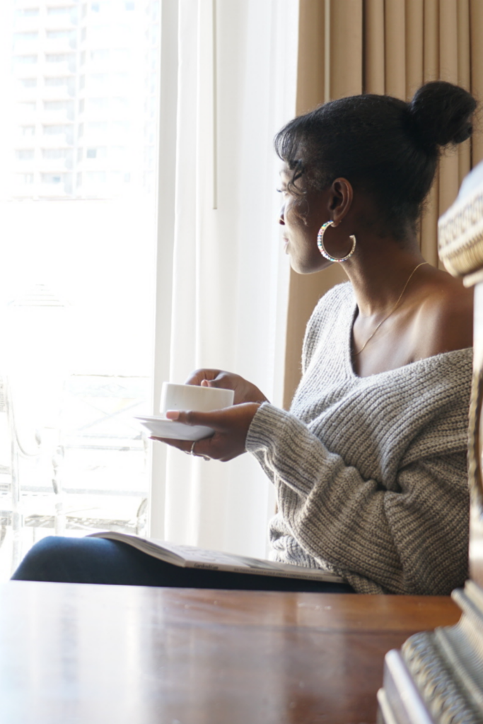 woman drinks coffee and looks out the window